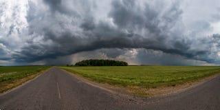 Panorama de Hdr sur la route goudronnée parmi des champs dans la soirée avec les nuages noirs impressionnants avant tempête image libre de droits