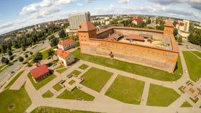 Panorama de la ciudad de Lida con un castillo Silueta del hombre de negocios Cowering Fotografía de archivo libre de regalías
