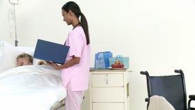 Panorama de la enfermera afroamericana que habla con un pequeño paciente almacen de video