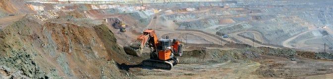 Panorama de la mina del mineral de hierro con un excavador Imágenes de archivo libres de regalías