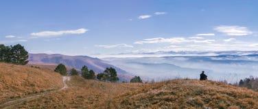 Panorama de la montaña con la hierba amarilla, los árboles y el cielo azul El sentarse y mirada en la silueta del hombre de la di Foto de archivo