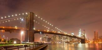 Panorama de la noche de New York City con el puente de Brooklyn Imagen de archivo