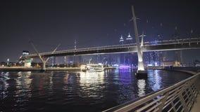 Panorama de la noche de Dubai y de un barco flotante en el fondo del puente del canal del Griego de Dubai almacen de video