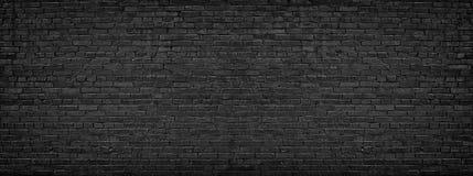 Panorama de la pared de ladrillo negra para los casquillos del sitio como fondo foto de archivo libre de regalías