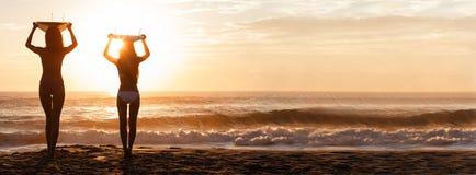 Panorama de la playa de la puesta del sol de las personas que practica surf y de las tablas hawaianas de las mujeres del bikini fotos de archivo libres de regalías