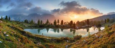 Panorama de la puesta del sol del lago de las montañas de la montaña en dolomías Imagen de archivo