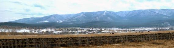Panorama de las montañas y de un pequeño pueblo en invierno Fotografía de archivo libre de regalías