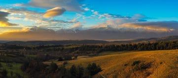 Panorama de los picos y del cielo azul con las nubes, Bulgaria de la nieve de la cordillera de Pirin Imagen de archivo