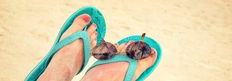 Panorama de los pies desnudos arenosos de la mujer con las chancletas y las gafas de sol, estilo del vintage Imagen de archivo libre de regalías