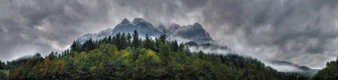 Panorama de montañas nubladas y de un bosque Foto de archivo libre de regalías