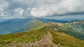 Panorama de montes verdes e da estrada de pedra em montanhas Carpathian no verão Fundo da paisagem das montanhas Imagem de Stock Royalty Free