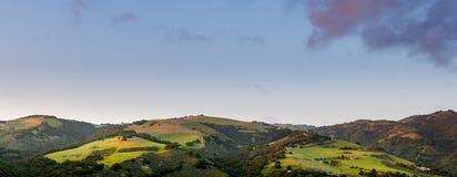 Panorama de montes verdes, de montanhas, e de campos bonitos na luz do por do sol sob um céu azul com nuvens roxas fotos de stock royalty free