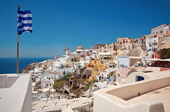 Panorama de Oia e bandeira grega Imagem de Stock