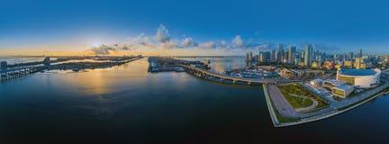 Panorama de photo de Miami-ville au coucher du soleil au crépuscule avec des gratte-ciel de ville et un pont au-dessus de la mer  Photo stock