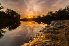Panorama de rivière sauvage avec la réflexion de ciel nuageux de coucher du soleil, en automne Photographie stock libre de droits