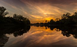 Panorama de rivière sauvage avec la réflexion de ciel nuageux de coucher du soleil, en automne Images libres de droits