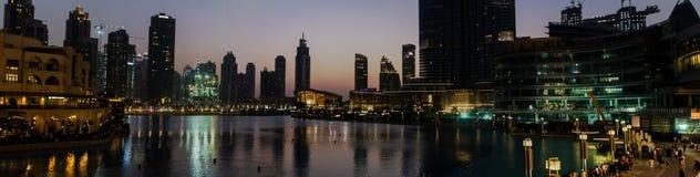 Panorama de skyscrappers e de construções iluminados em torno de um lago em Fotos de Stock