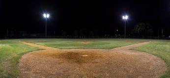 Panorama de terrain de base-ball vide la nuit par derrière le pâté à la maison Image stock