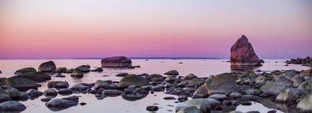 Panorama de um por do sol bonito sobre um litoral rochoso Foto de Stock