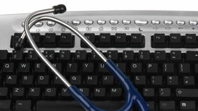 Panorama de un estetoscopio en un teclado almacen de metraje de vídeo