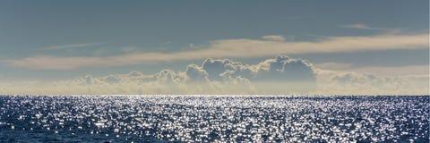 Panorama de un paisaje marino en madrugada con los puntos ligeros chispeantes numerosos en el agua y un cielo hermoso foto de archivo libre de regalías