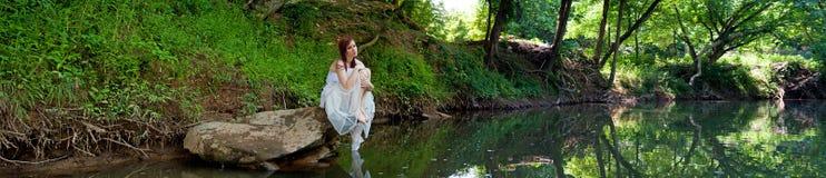 Panorama de una novia triste que se sienta en una roca Foto de archivo