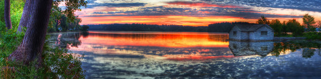 Panorama de una salida del sol en un lago Fotos de archivo libres de regalías