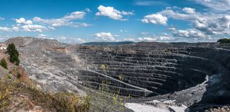Panorama of the deep open stone pit at the noon. Great open stone pit with spiral road Royalty Free Stock Image