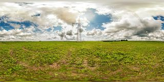 Panorama 360 degrees angle view near high voltage electric pylon towers in field with beautiful clouds in equirectangular. Projection, skybox VR AR content stock images