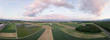 Panorama dei campi e del lago verdi Fotografie Stock
