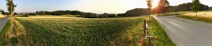 Panorama del campo del paese al tramonto con una bici di velocità Fotografia Stock Libera da Diritti
