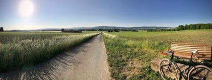 Panorama del campo del paese con una bici di velocità su una strada campestre Immagini Stock