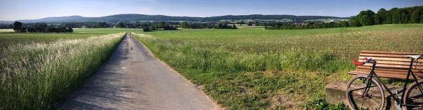 Panorama del campo del paese con una bici di velocità su una strada campestre Fotografia Stock