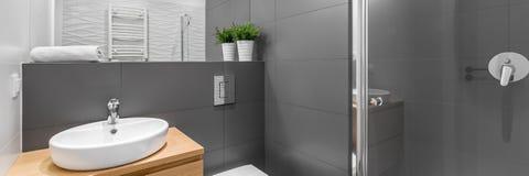Panorama del cuarto de baño gris moderno con la ducha imagenes de archivo