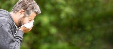 Panorama del hombre que estornuda Foto de archivo libre de regalías