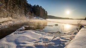 Panorama del invierno del lago congelado en un bosque nevoso con la niebla sobre el agua, Rusia, Fotos de archivo