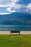 Panorama del lago Como y de las montan@as con el banco Foto de archivo