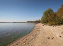 Panorama del lago, con più fodrest e cielo blu Fotografia Stock