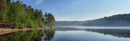 Panorama del lago dello specchio con una casa sola sulla riva Immagine Stock