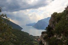 Panorama del lago Garda y de montañas con las nubes de tormenta oscuras, Italia Fotos de archivo