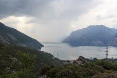 Panorama del lago Garda y de montañas con las nubes de tormenta oscuras, Italia Fotografía de archivo