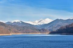Panorama del lago mountain contro il cielo nuvoloso e le montagne coperti Fotografie Stock