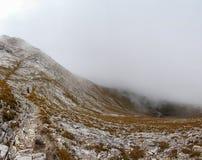 Panorama del pendio di montagna della nebbia di viaggiatore con zaino e sacco a pelo Immagini Stock