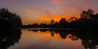 Panorama del río salvaje con la reflexión del cielo nublado de la puesta del sol, en otoño Foto de archivo