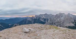 Panorama dell'aumento del sole dietro la cresta della montagna Immagine Stock