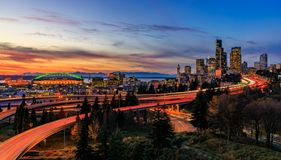 Panorama dell'orizzonte del centro di Seattle oltre lo scambio dell'autostrada senza pedaggio di I-5 I-90 al tramonto con le luci fotografia stock