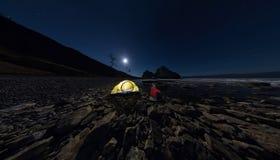 Panorama dell'uomodi alla tendadi sulla spiaggiadella pietra di sulla riva delle sedere del lago Immagine Stock