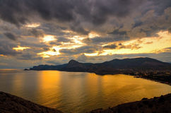 Panorama della baia di Sudak, nella penombra, su un tramonto dorato Immagini Stock