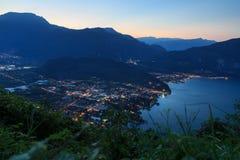 Panorama della città di Riva del Garda alla polizia ed alle montagne del lago alla notte prima di alba Fotografia Stock