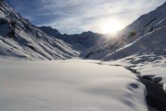 Panorama della montagna con neve, il piccolo fiume ed il sole nell'inverno nelle alpi di Stubai Fotografia Stock